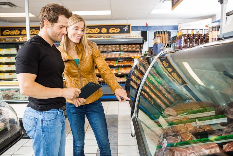 Paare, die Fleisch vom Verkaufsmöbel wählen stockbild