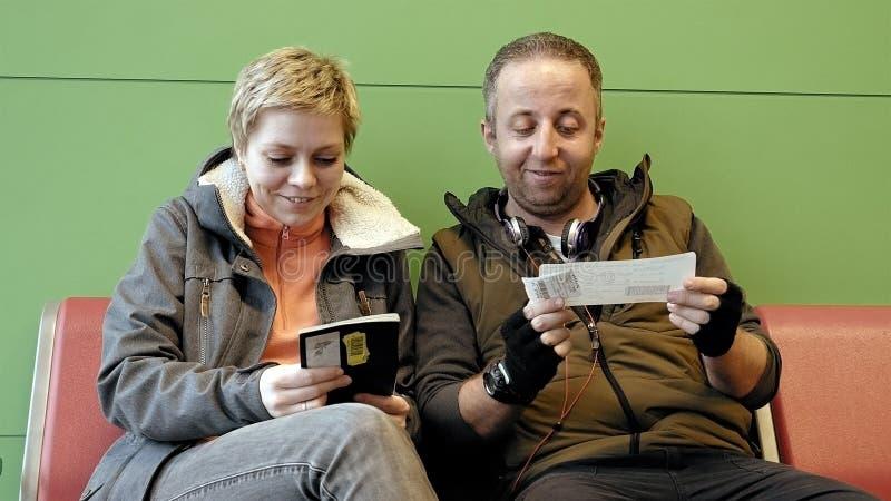 Paare, die am Flughafenabfertigungsgebäude mit Karten warten lizenzfreies stockfoto