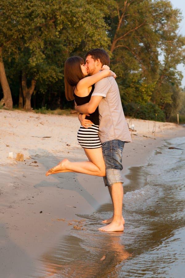 Paare, die am Flussufer umarmen und küssen stockbild