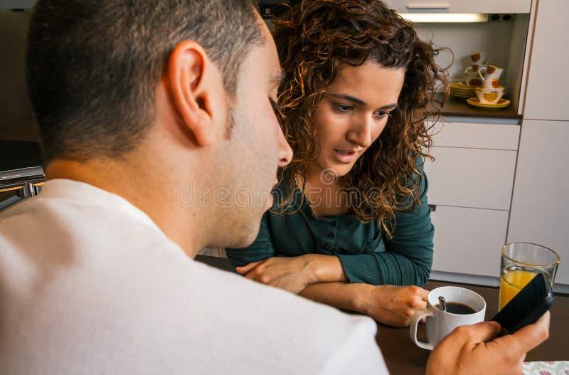 Paare, die frühstücken und beweglich schauen stockfoto