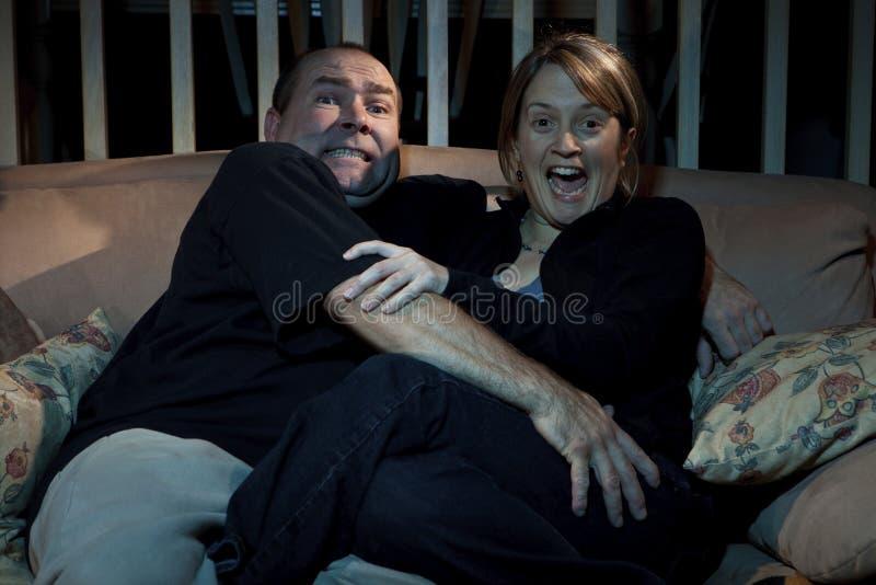 Paare, die furchtsamen Film auf Fernsehapparat überwachen stockfotos