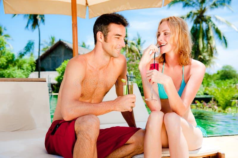 Paare, die Getränke durch das Pool haben lizenzfreie stockfotografie