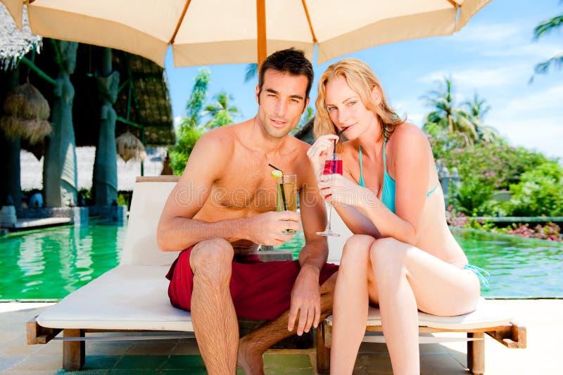 Paare, die Getränke durch das Pool haben stockbilder