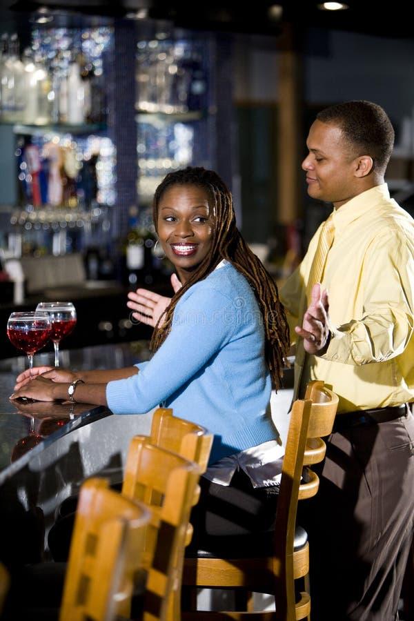 Paare, die Getränke am Stab genießen lizenzfreies stockfoto