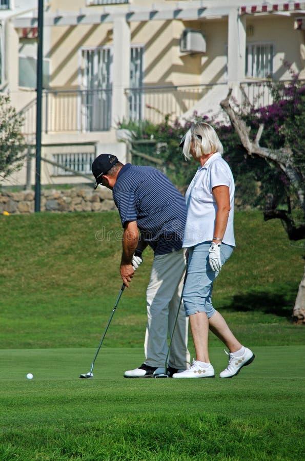 Paare, die Golf, Caleta de Velez spielen stockfotografie