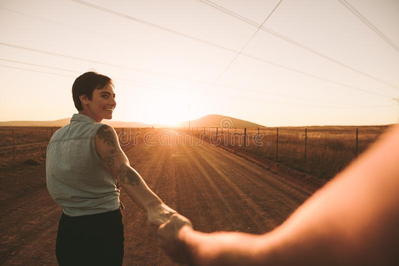 Paare, die Hand in Hand auf Landstraße gehen stockbild