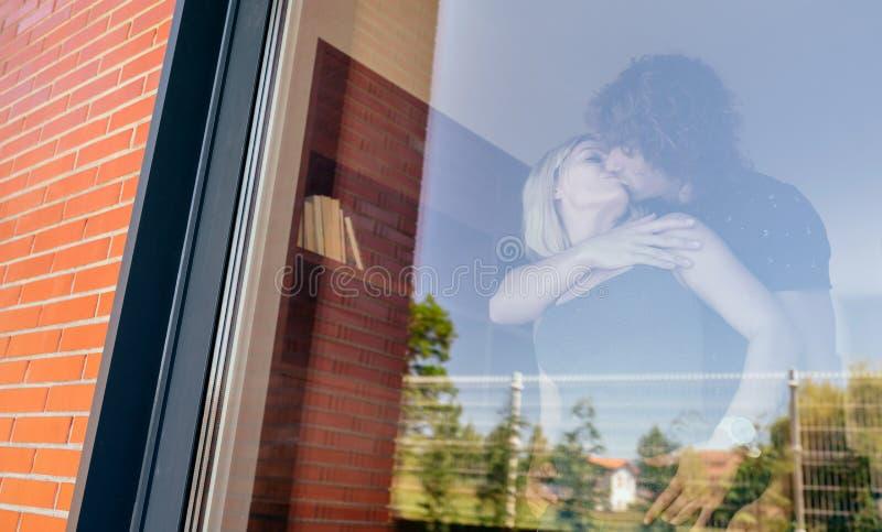 Paare, die hinter dem Fenster küssen lizenzfreie stockbilder