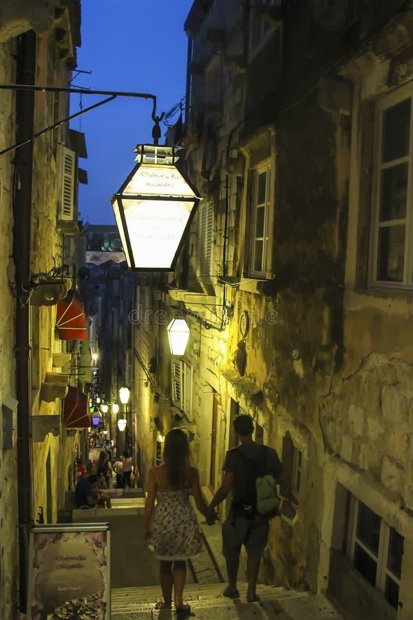Paare, die hinunter steile Treppen in der alten Stadt von Dubrovnik nachts gehen lizenzfreie stockbilder