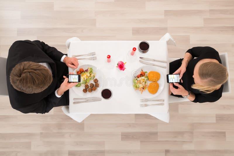 Paare, die ihre Handys betrachten lizenzfreie stockfotos