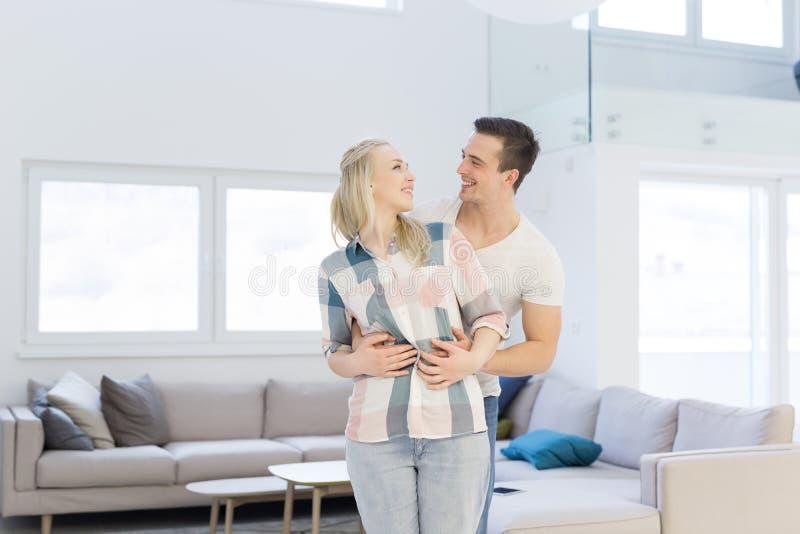 Paare, die in ihrem neuen Haus umarmen stockbild