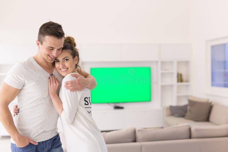 Paare, die in ihrem neuen Haus umarmen stockfotos
