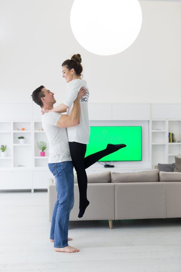 Paare, die in ihrem neuen Haus umarmen stockfotografie