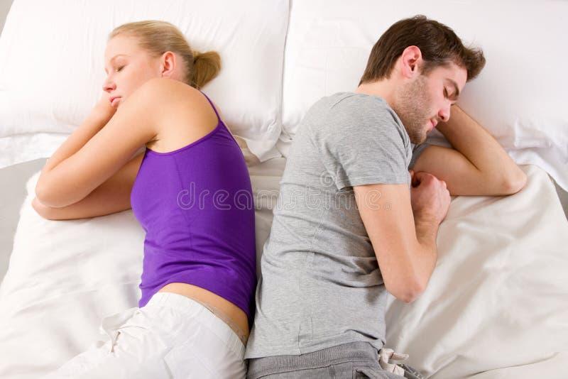Paare, die im Bett Wechsel liegen stockbild