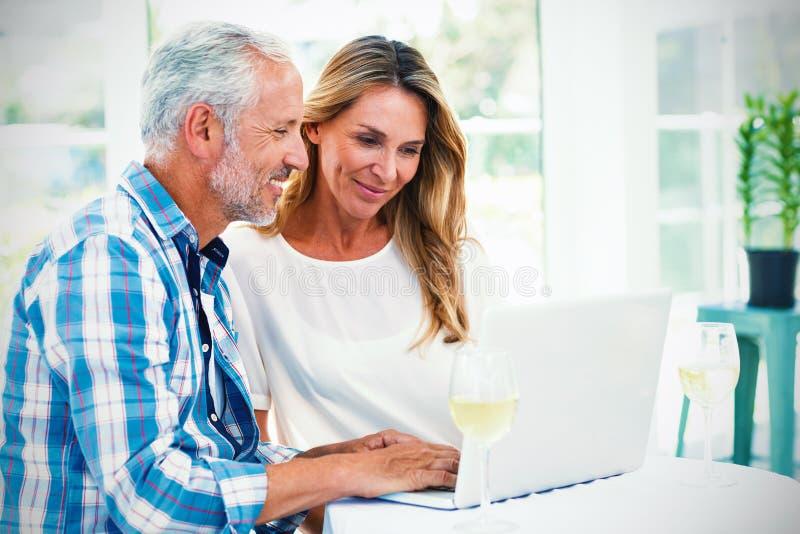 Paare, die im Laptop auf Tabelle schauen vektor abbildung