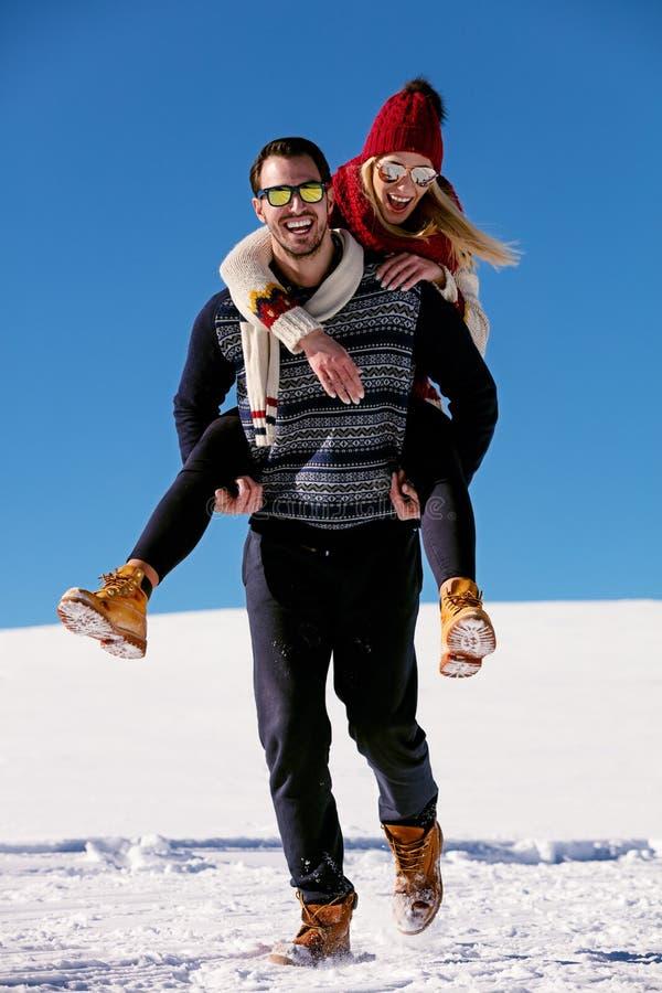 Paare, die im Schnee spielen Mann, der Frauendoppelpolfahrt auf Winterferien gibt stockbild