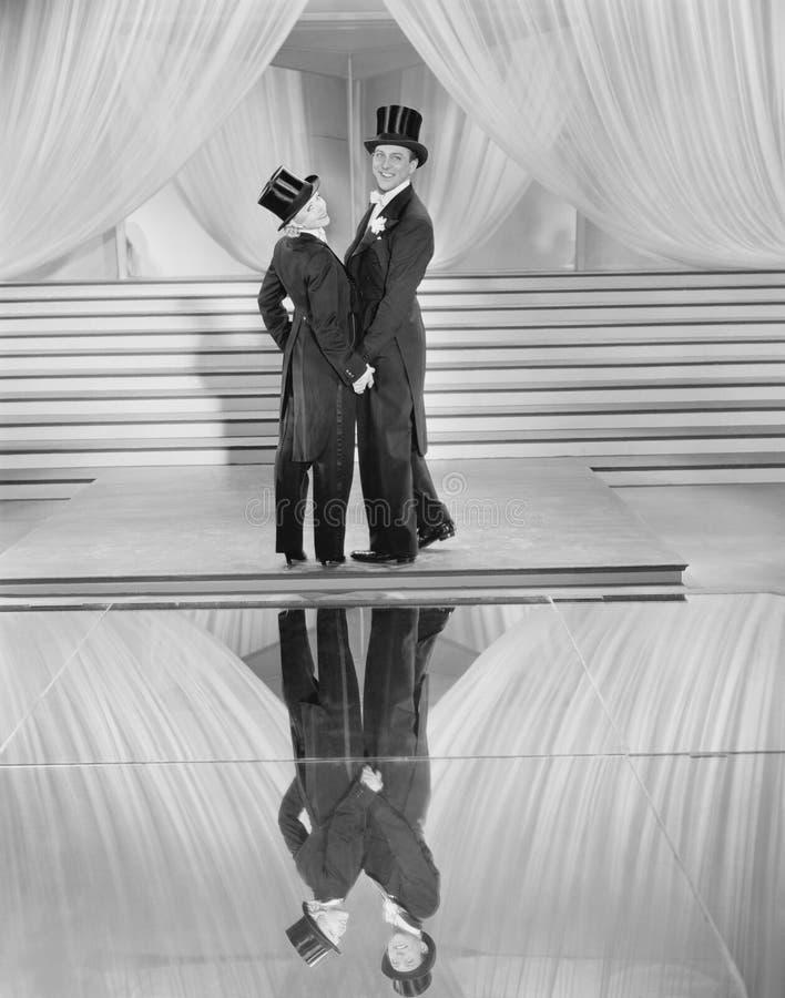 Paare, die im Smoking und in der Reflexion (alle dargestellten Personen, aufwerfen sind nicht längeres lebendes und kein Zustand  lizenzfreie stockbilder
