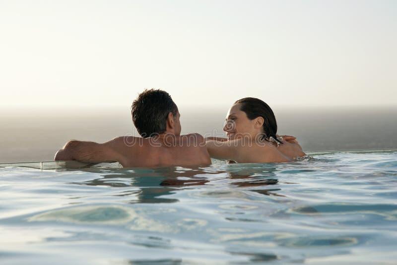 Paare, die im Unendlichkeits-Pool am Erholungsort sich entspannen stockbild