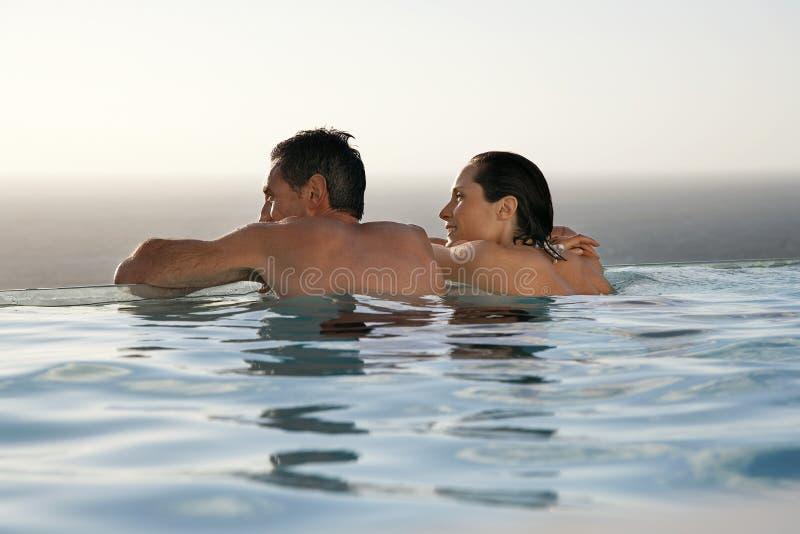 Paare, die im Unendlichkeits-Pool am Erholungsort sich entspannen stockfoto