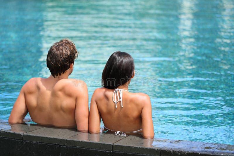 Paare, die im UnendlichkeitsSwimmingpoolerholungsort sich entspannen lizenzfreies stockbild