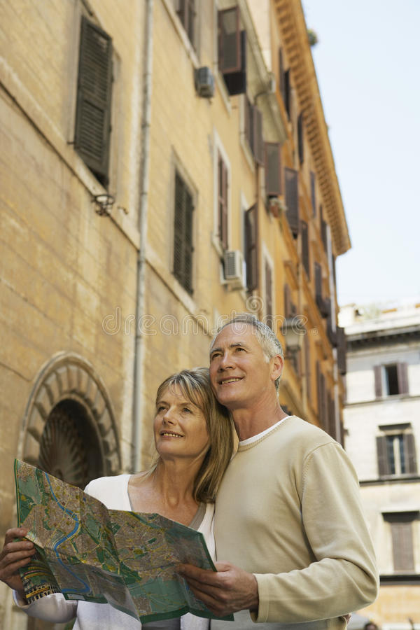 Paare, die Karte auf Straße in Rom halten lizenzfreies stockfoto