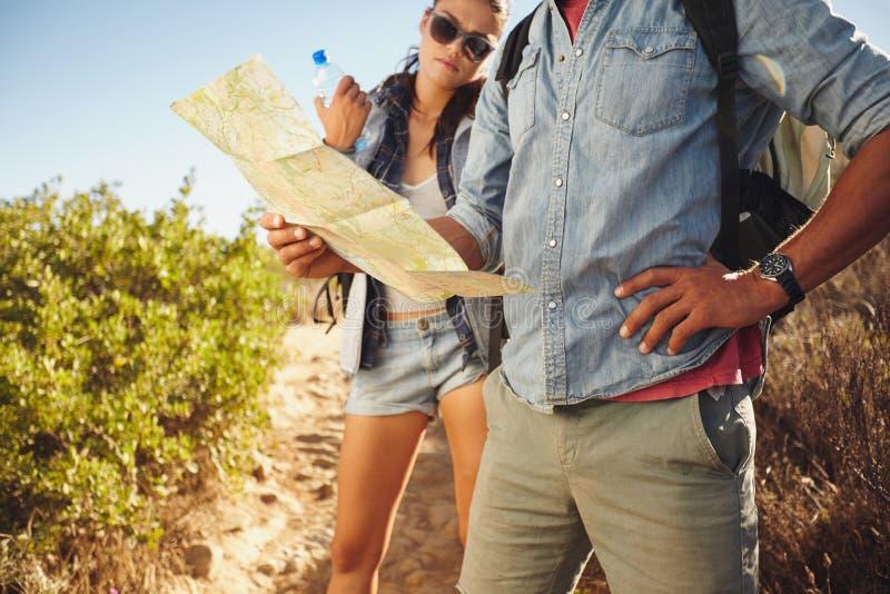 Paare, die Karte beim Wandern überprüfen stockfotografie