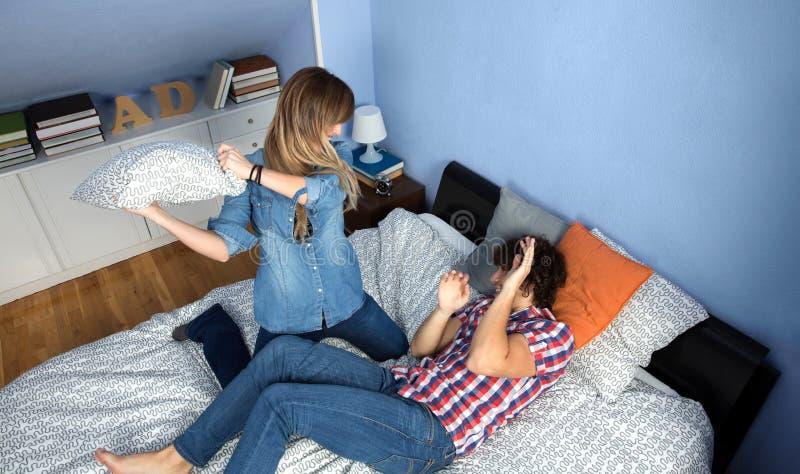 Paare, die Kissenschlacht auf dem Bett machen lizenzfreies stockbild