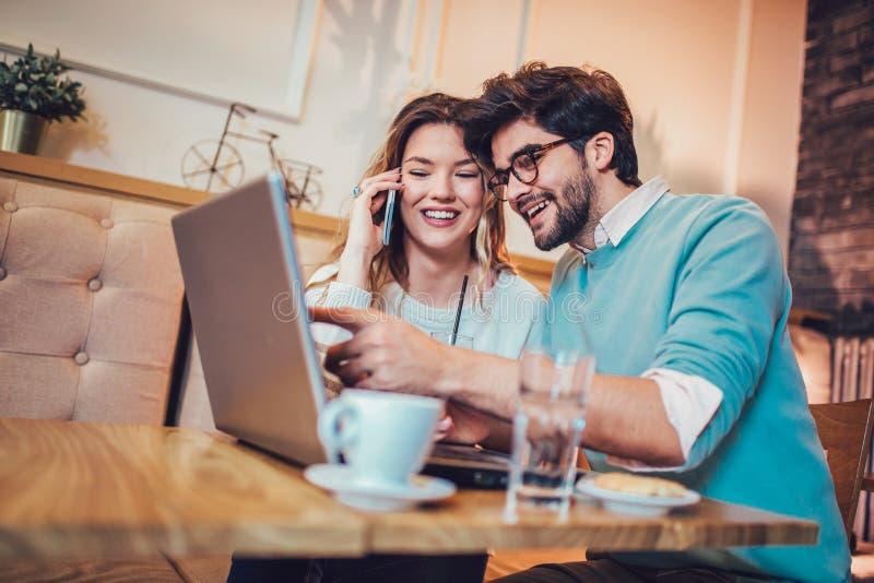 Paare, die an Laptop im Café arbeiten stockfotos