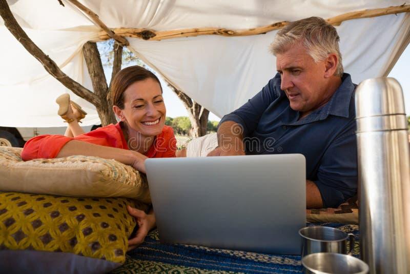Paare, die Laptop im Zelt betrachten stockbilder