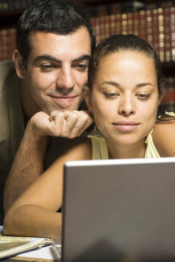 Paare, die an Laptop - Vertikale arbeiten stockfoto