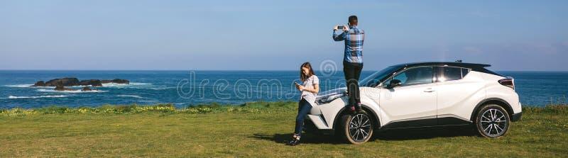 Paare, die mit dem Auto reisen, die Landschaft fotografierend lizenzfreie stockbilder