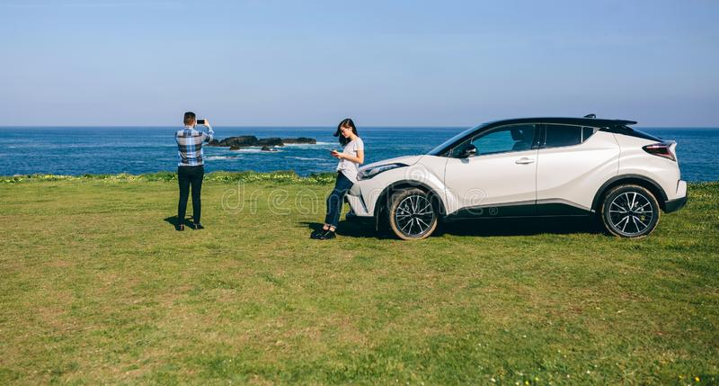 Paare, die mit dem Auto reisen, die Landschaft fotografierend lizenzfreies stockfoto