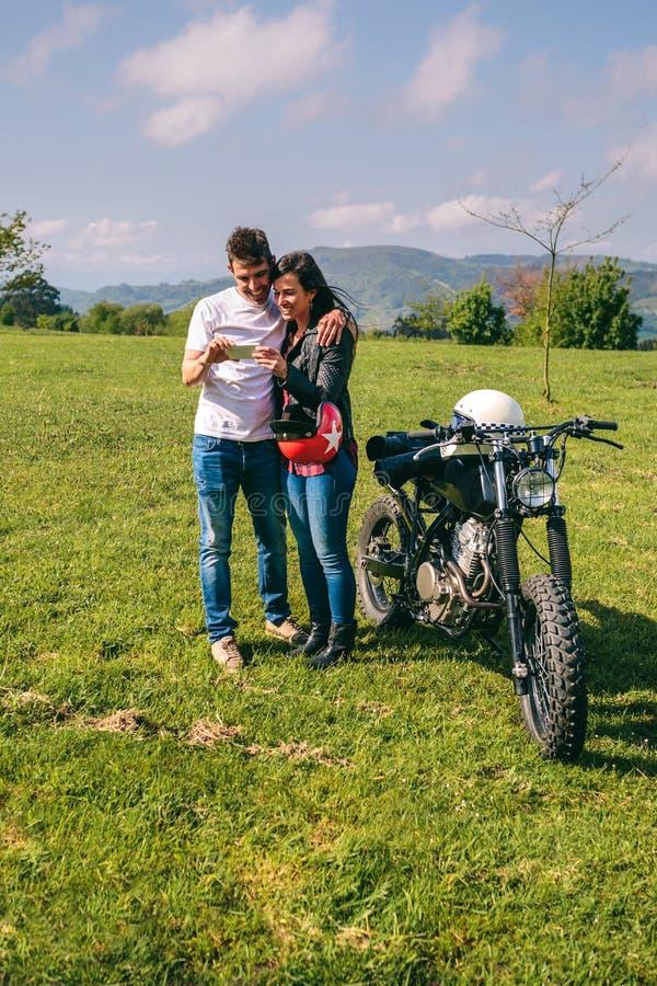 Paare, die mit einem Motorrad beweglich schauen lizenzfreies stockfoto