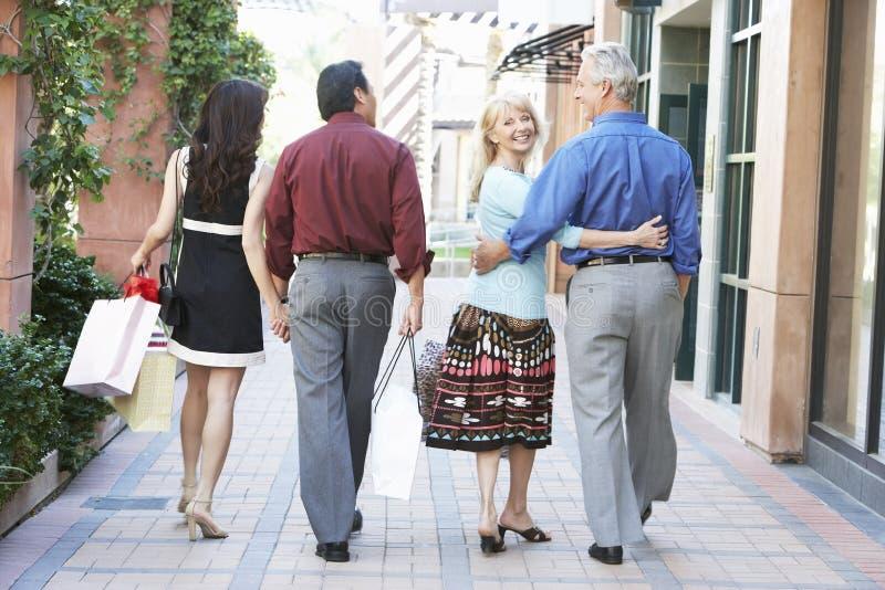 Paare, die mit Einkaufstaschen gehen stockfotos