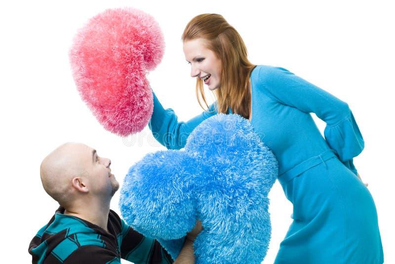 Paare, die mit Kissen kämpfen lizenzfreie stockbilder