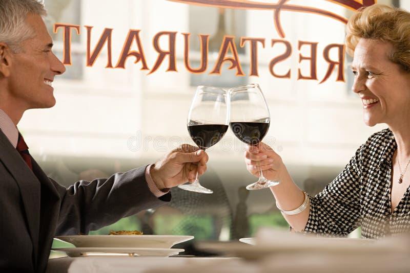 Paare, die mit Wein rösten lizenzfreie stockfotos