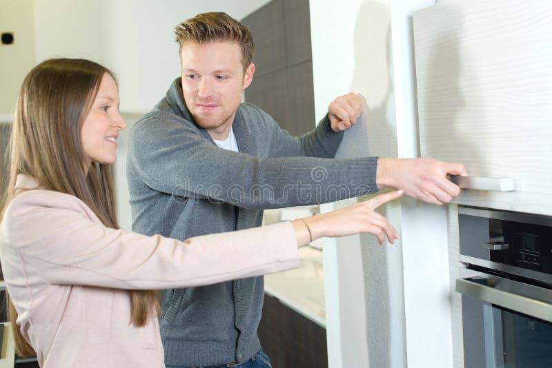 Paare, die moderne Küchenmöbel wählen stockfotos