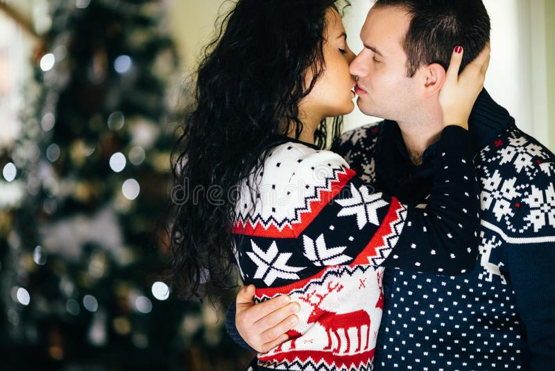 Paare, die nahe bei Weihnachtsbaum küssen lizenzfreies stockfoto