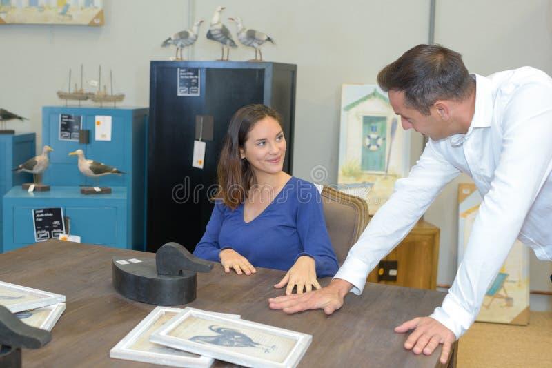 Paare, die neue hölzerne Tabelle betrachten stockbilder