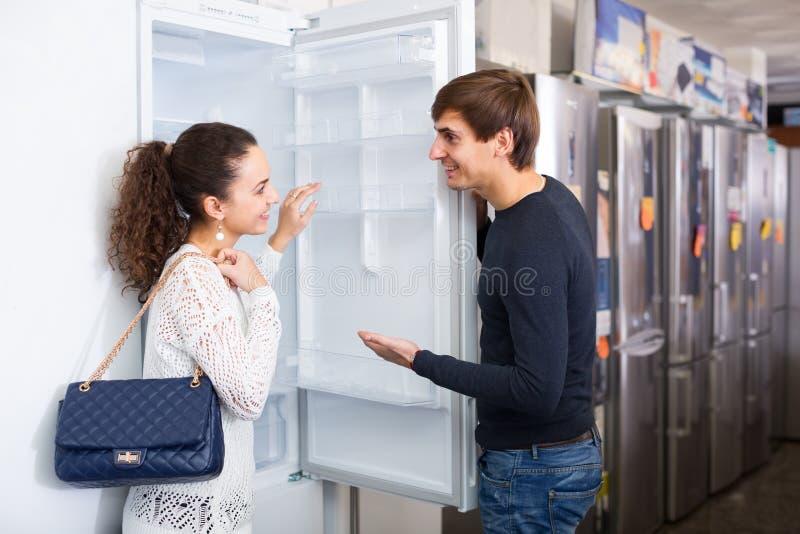 Paare, die neuen Kühlschrank wählen stockfoto