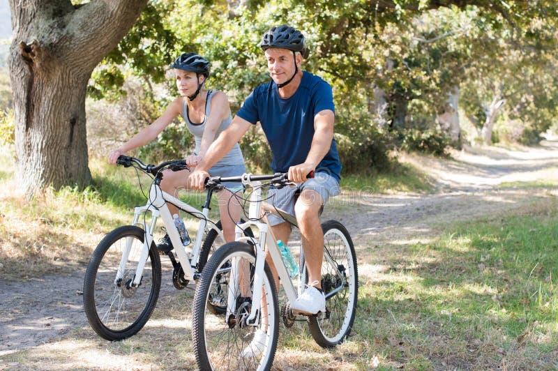 Paare, die am Park radfahren stockfoto