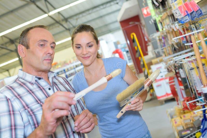 Paare, die Pinsel im Baumarkt wählen stockfoto