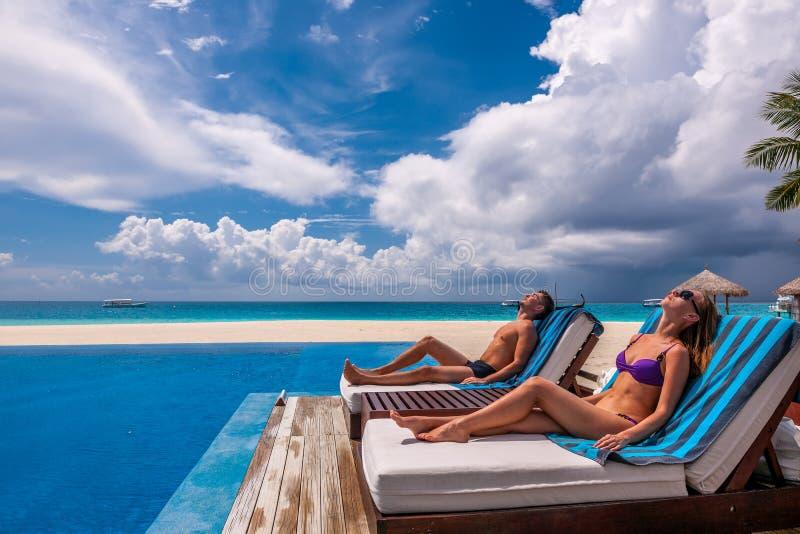 Paare, die am Poolside sich entspannen lizenzfreie stockfotografie