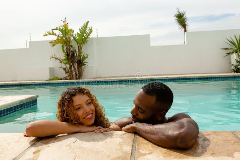 Paare, die am Rand eines Swimmingpools an einem sonnigen Tag sich lehnen lizenzfreie stockfotos