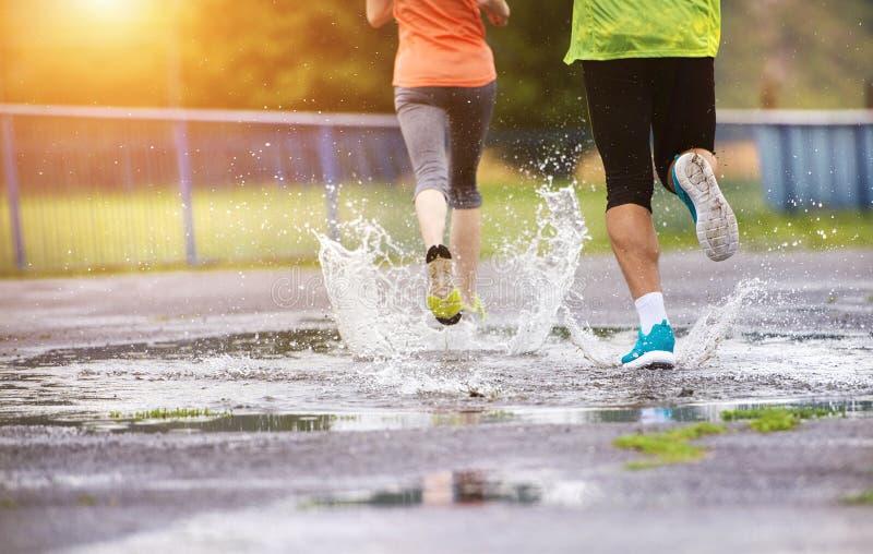 Paare, die in regnerisches Wetter laufen lizenzfreies stockfoto