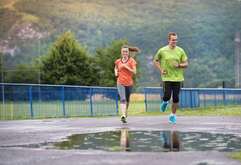 Paare, die in regnerisches Wetter laufen lizenzfreie stockfotografie