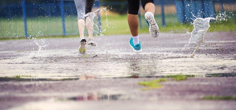 Paare, die in regnerisches Wetter laufen lizenzfreie stockfotos