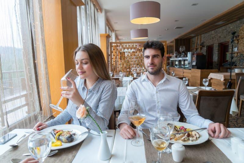 Paare, die am rustikalen feinschmeckerischen Restaurant zu Mittag essen stockbild