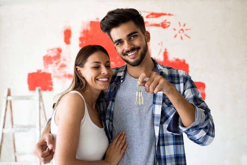 Paare, die Schlüssel des dort neuen Hauses halten stockbild