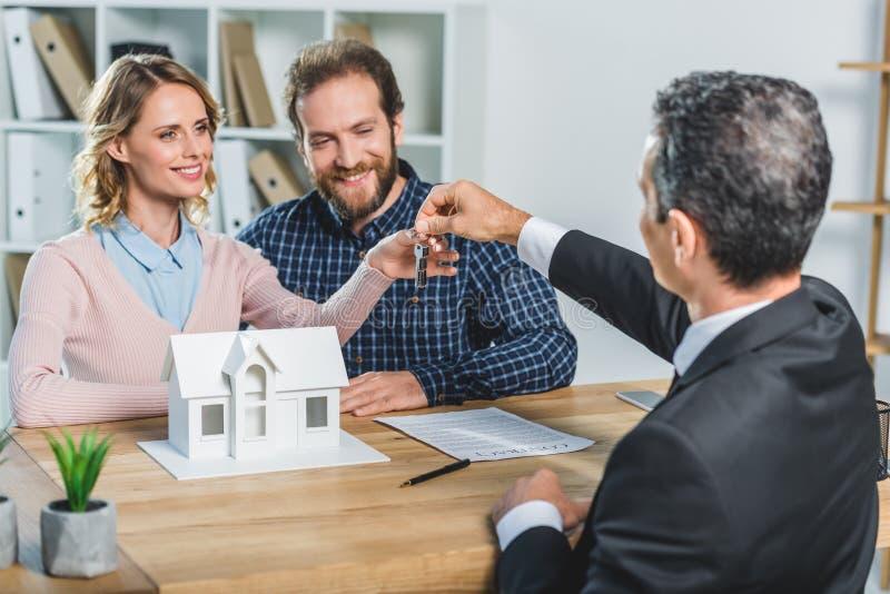 Paare, die Schlüssel vom Grundstücksmakler erhalten stockbilder