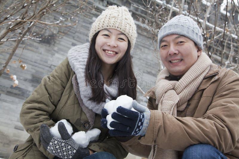 Paare, die Schneebälle im Park halten stockfotos